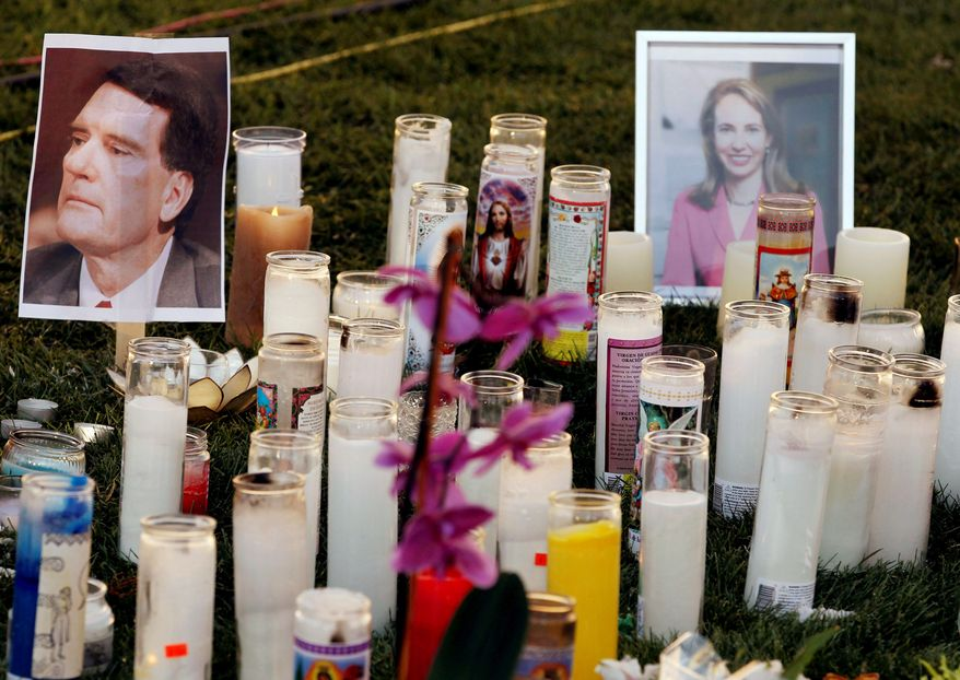 TRIBUTE: A makeshift memorial outside the University Medical Center in Tucson, Ariz., honors the victims of Saturday's shooting rampage in that city during a speech by Democratic U.S. Rep. Gabrielle Giffords (upper right), who was shot through the head but is expected to survive. U.S. District Judge John M. Roll (upper left) and five others, including a 9-year-old girl, were killed by a gunman. (Associated Press)