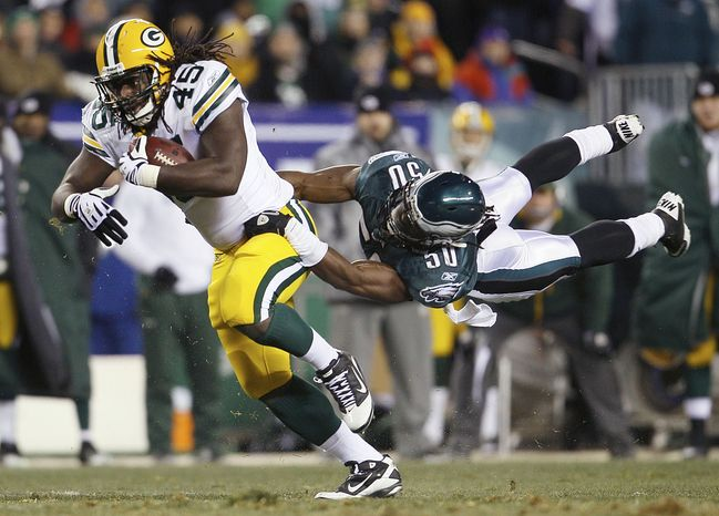 Green Bay Packers fullback Quinn Johnson pulls Philadelphia Eagles linebacker Ernie Sims along after a pass reception during the first half of an NFL football NFC wild-card playoff game in Philadelphia, Sunday, Jan. 9, 2011. (AP Photo/Matt Slocum)
