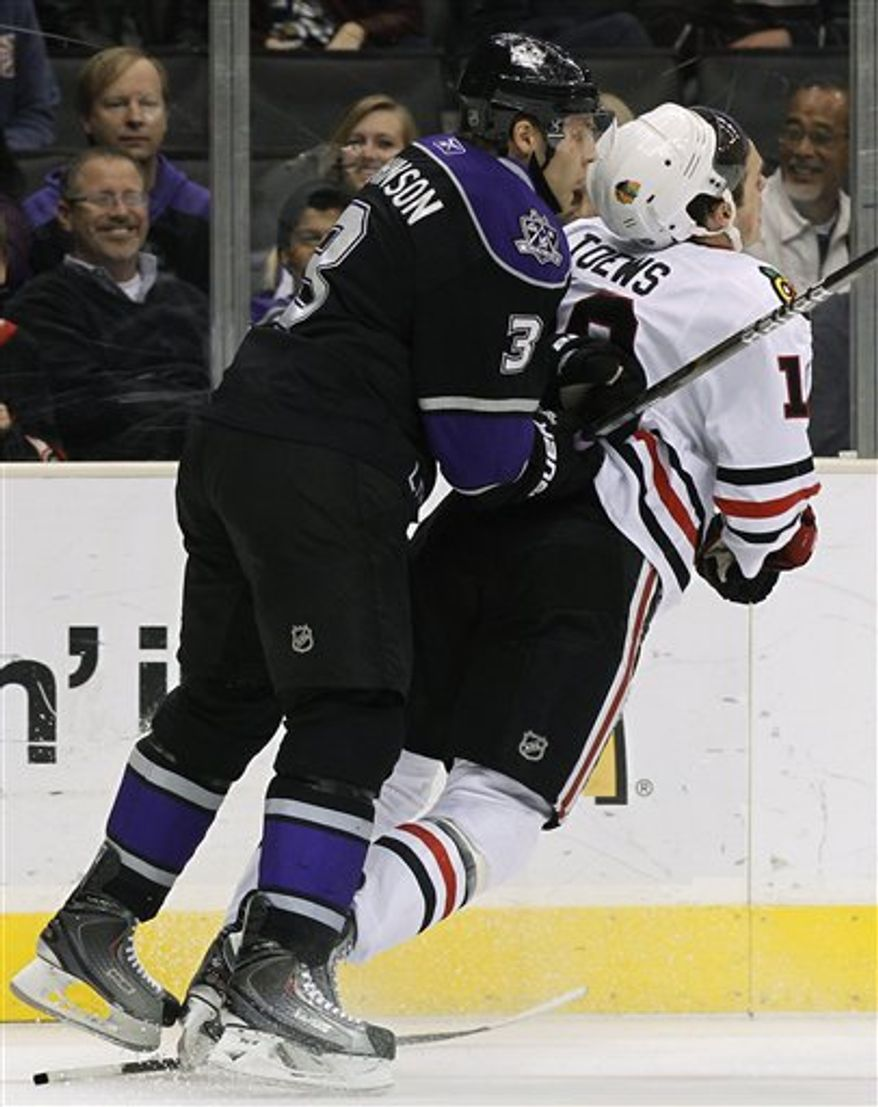 Los Angeles Kings' Jack Johnson, left, checks Chicago Blackhawks' Jonathan Toews during the first period of an NHL hockey game in Los Angeles on Monday, Jan. 3, 2011. (AP Photo/Danny Moloshok)