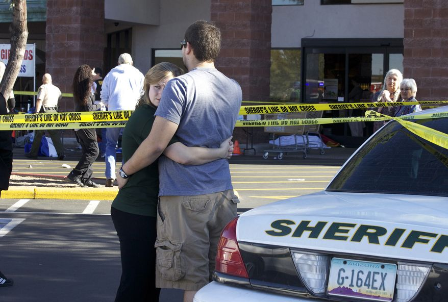 Two people embrace each other Saturday at the scene where Rep. Gabrielle Giffords, Arizona Democrat, and others were shotoutside a Safeway grocery store in Tucson, Ariz. (Associated Press)