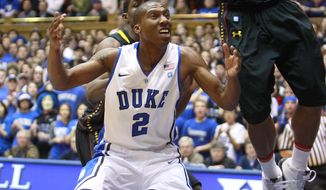 Maryland's Sean Mosley (14) and Duke's Nolan Smith (2) reach for a rebound during the first half of an NCAA college basketball game in Durham, N.C., Sunday, Jan. 9, 2011. (AP Photo/Gerry Broome)