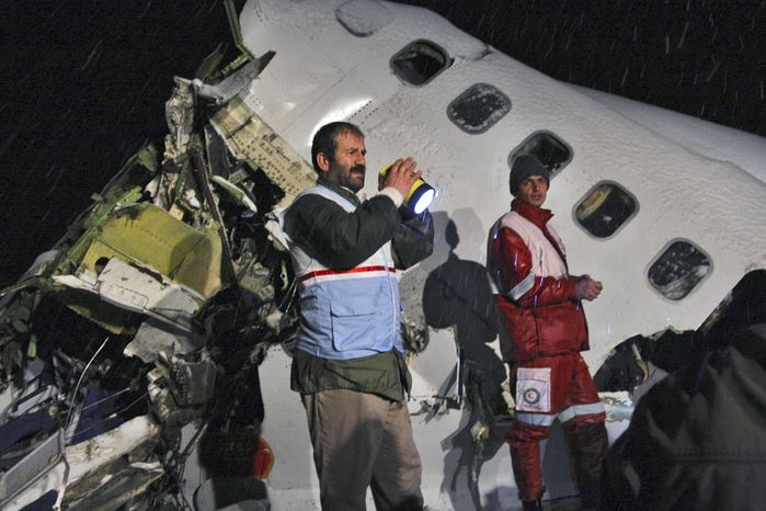 In this picture released by the Mehr news agency, rescue workers attend the scene Sunday after an IranAir Boeing 727 passenger plane crashed as it was making an emergency landing outside the city of Orumiyeh, 460 miles northwest of Tehran. An IranAir passenger jet carrying 106 people crashed as it was making an emergency landing Sunday in a snowstorm in the country's northwest and broke into several pieces, killing more than 70 of those on board, Iranian media reported. The others survived with light injuries. (Associated Press/Mehr News Agency, Esfandiar Asgharkhani)