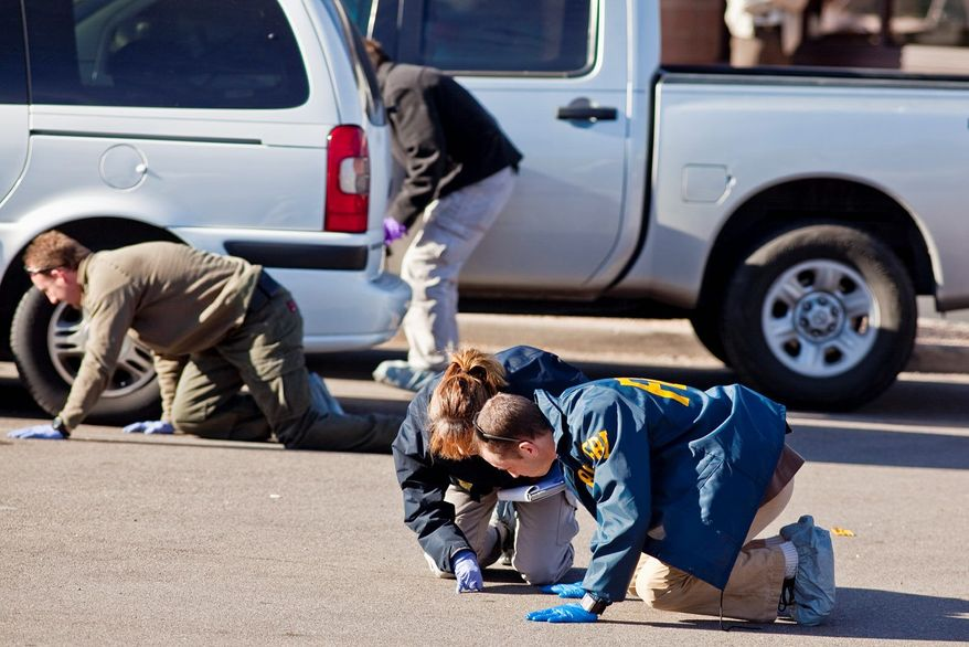 FBI agents and Tucson area law enforcement officers scour the parking lot of the Safeway in Tucson, Ariz., on Monday, looking for evidence of Saturday's shootings. Two days after a mass shooting at the Safeway, the grocery store is closed and the parking lot a scene of intense law enforcement activity. (Associated Press)