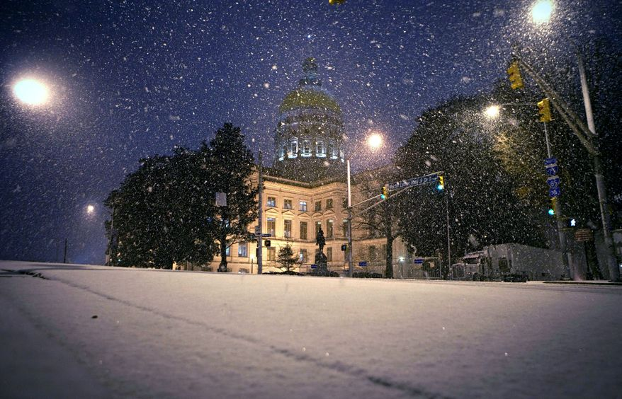 ** FILE ** Snow falls against the backdrop of the Georgia Capitol on Sunday, Jan. 9, 2011, in Atlanta. The inauguration of Gov.-elect Nathan Deal on Monday was moved indoors from the Capitol steps to the House chamber because of the weather. (AP Photo/David Goldman)
