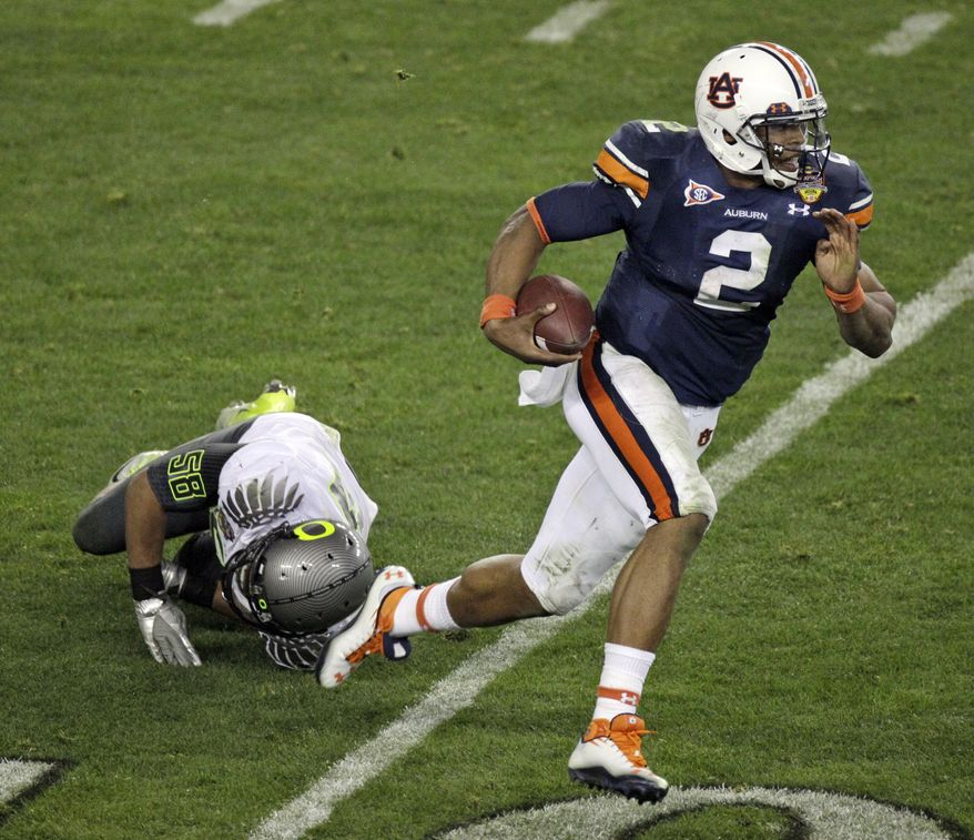 Auburn's Cam Newton (2) carries the ball as Oregon's Kenny Rowe (58) falls to the turf during the second half of the BCS National Championship NCAA college football game Monday, Jan. 10, 2011, in Glendale, Ariz. (AP Photo/Charlie Riedel)