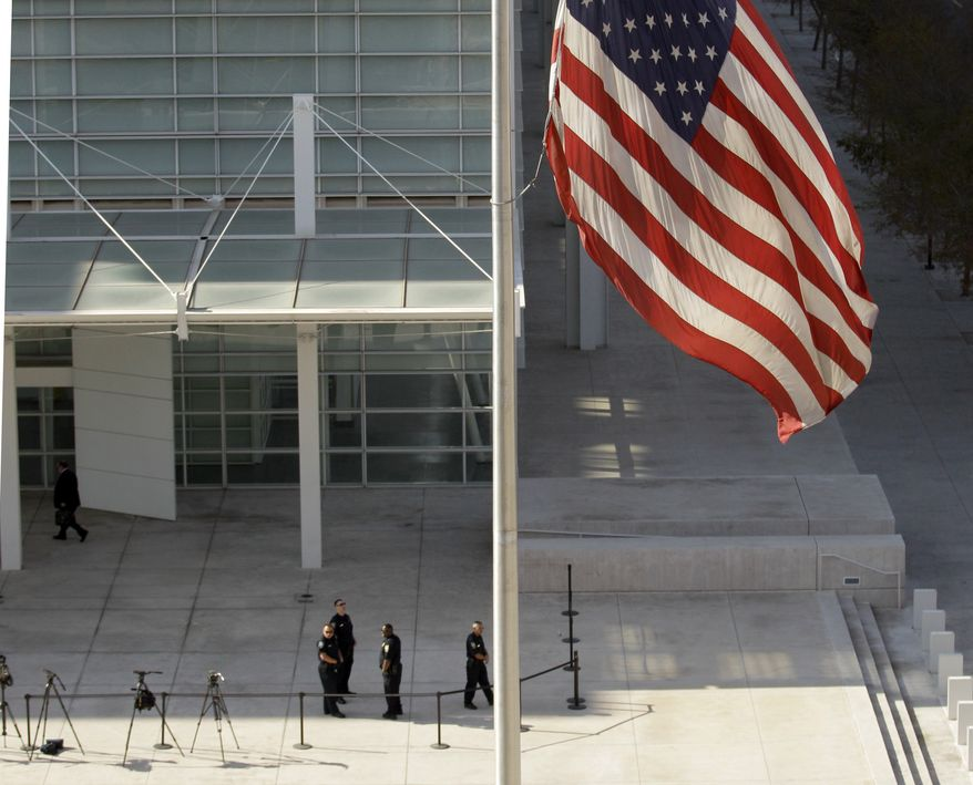 A flag stands at half-staff as security officials stand at the entrance to the the Sandra Day O'Connor United States Courthouse in Phoenix, Ariz., Monday, Jan. 10, 2011, where 22-year-old Jared Loughner is scheduled to appear in federal court on charges he tried to assassinate Rep. Gabrielle Giffords in a shooting rampage that left six people dead. (AP Photo/Charlie Riedel)