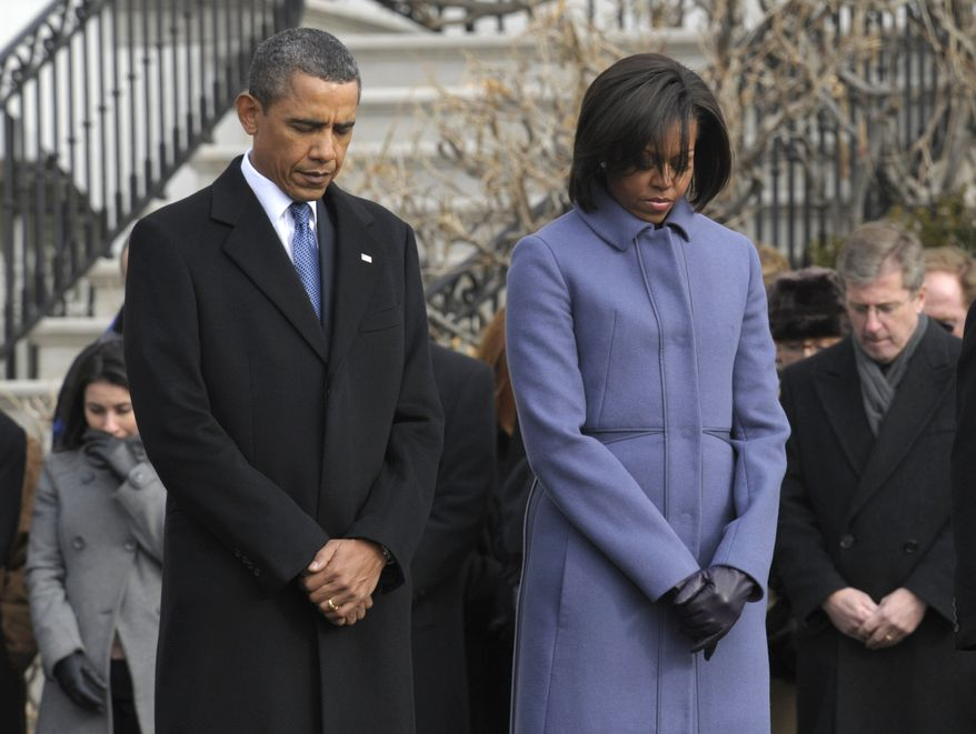 President Barack Obama, first lady Michelle Obama and government employees observe a moment of silence on South Lawn of the White House in Washington, Monday, Jan. 10, 2011, to honor those who were killed and injured in the shooting in Tucson, Ariz. Rep. Gabrielle Giffords, D-Ariz., is in critical condition after being shot in the head. (AP Photo/Susan Walsh)