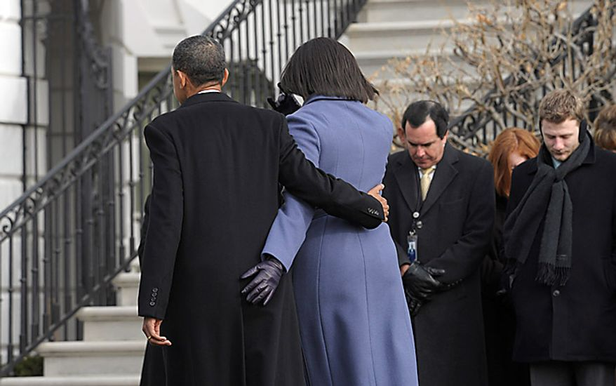 President Barack Obama and first lady Michelle Obama head back into the White House after observing a moment of silence with government employees on South Lawn of the White House in Washington, Monday, Jan. 10, 2011, to honor those who were killed and injured in the shooting in Tucson, Ariz. Rep. Gabrielle Giffords, D-Ariz., is in critical condition after being shot in the head. (AP Photo/Susan Walsh)