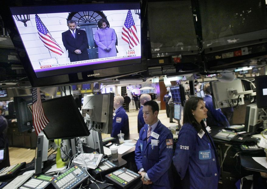 A television monitor shows President Obama and Michele Obama as he presides over a national moment of silence, while specialists on the trading floor of the New York Stock Exchange observe the occasion for severely injured Arizona Rep. Gabrielle Giffords and the people who were killed during an assassination attempt against her, Monday, Jan. 10, 2011. (AP Photo/Richard Drew)