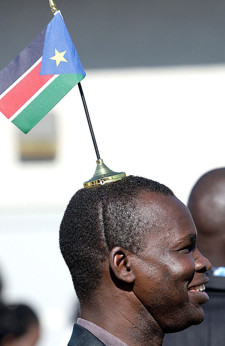 William Obur wears the flag of South Sudan on his head after casting his ballot in the South Sudan referendum election at an out-of-country voting precinct on Sunday, Jan. 9, 2011, in Glendale, Ariz. (AP Photo/Ross D. Franklin)