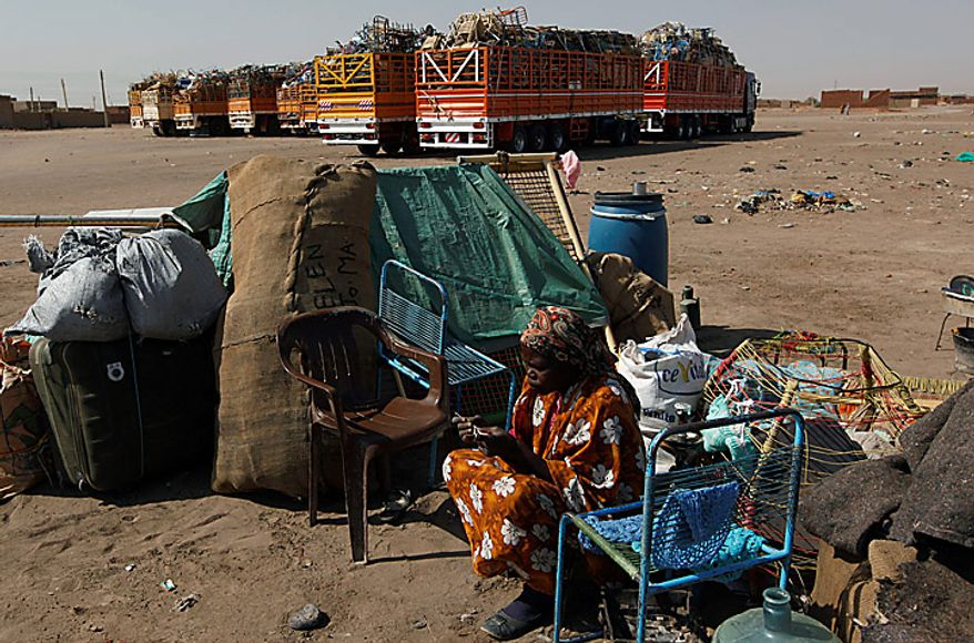 A Southern Sudanese woman sits by her belongings at a bus station on the outskirts of Khartoum, Sudan, on Monday, Jan. 10, 2011, as she waits for transportation back home. (AP Photo/Nasser Nasser)