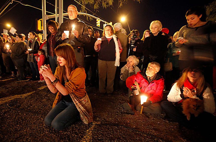 Well-wishers gather for a candle light vigil outside the offices U.S. Rep. Gabrielle Giffords, Arizona Democrat, in Tucson, Ariz., Sunday, Jan. 9, 2011. Mrs. Giffords was critically wounded during a shooting at a political event Saturday, Jan. 8, 2011 in Tucson, Ariz. (AP Photo/Chris Carlson)