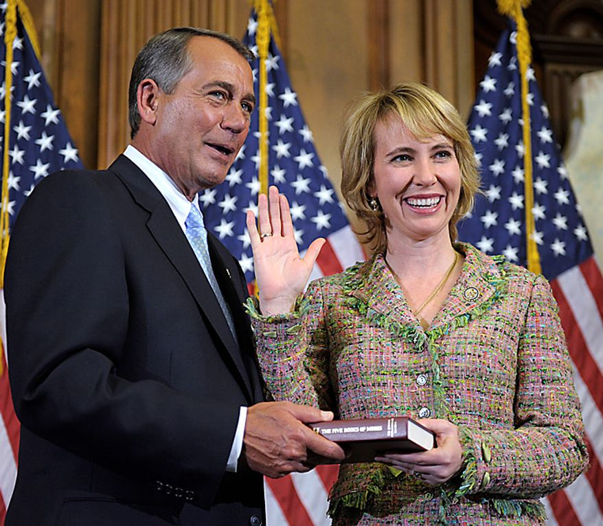 In this Jan. 5, 2011, file photo, House Speaker John Boehner re-enacts the swearing in of Rep. Gabrielle Giffords, Arizona Democrat, on Capitol Hill in Washington. Mrs. Giffords was shot in the head on Saturday, Jan. 8, 2011, while meeting with constituents in her district in the area around Tucson. (AP Photo/Susan Walsh, File)
