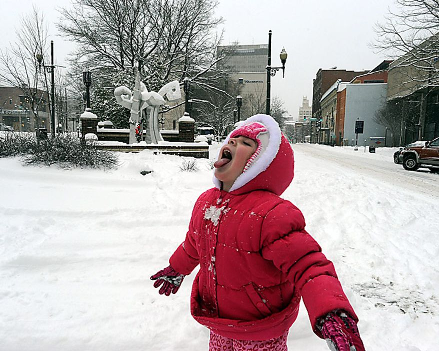 Livia Soares, 4,  of Gainsville, Fla., samples her first snow at Pritchard Park in Asheville, N.C., Monday, Jan. 10, 2011, while visiting Asheville with her father, Andre, and mother Lisiane. The couple moved to Florida from tropical  Brazil and, like their daughter, they had never seen snow and came to Asheville when they heard the storm was coming. (AP Photo/Asheville Citizen-Times, John Coutlakis)