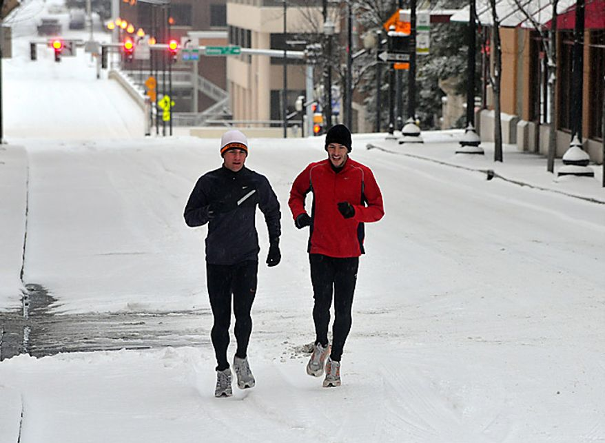 Two runners brave the snow Monday, Jan. 10, 2011, in Knoxville, Tenn. The National Weather Service has posted a winter weather advisory for most of East Tennessee with significant snowfall accumulations expected. (AP Photo/ J. Miles Cary, Knoxville News Sentinel)
