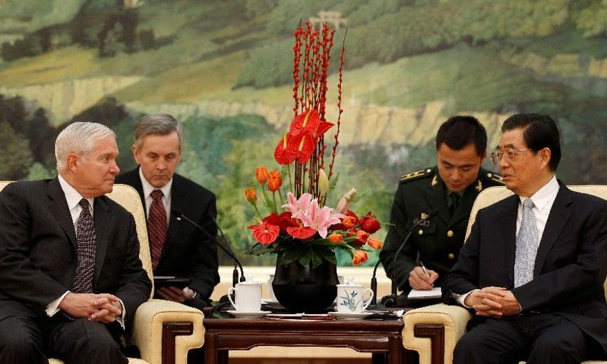 U.S. Secretary of Defense Robert M. Gates (left front) listens to Chinese President Hu Jintao during a meeting Tuesday at the Great Hall of the People in Beijing. Mr. Hu visits the U.S. later this month. (Associated Press)