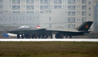 **FILE** People surround a Chinese military J-20 stealth jet Jan. 5, 2011, before it undergoes a runway taxi test in Chengdu, China. (Associated Press)