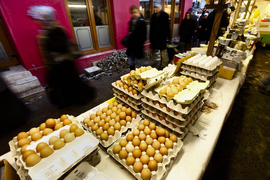People pass a market stall with eggs at a farmers market in Berlin on Friday, Jan. 7, 2011. German authorities ordered hundreds of pigs slaughtered Tuesday, Jan. 11, 2011, after tests showed high levels of a cancer-causing chemical for the first time in swine, as the nation's dioxin scandal widened beyond poultry and eggs.(AP Photo/Markus Schreiber)