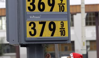**FILE** In this Dec. 6 photo, a man with a Santa cap looks up at a marquee with high gas prices at a Shell gas station in San Francisco. (Associated Press)