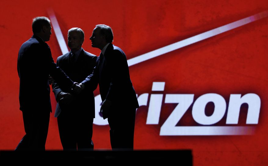Consumer Electronics Association president and Chief Executive Officer Gary Shapiro, left, greets Verizon Communications Inc., chairman and Chief Executive Officer Ivan Seidenberg, right, and president and Chief Operating Officer Lowell McAdam during the Consumer Electronics Show in Las Vegas on Jan. 6, 2011. As the tech industry awaits a likely Verizon iPhone announcement on Tuesday, Jan. 11, 2011,shares of Apple Inc. hit a record high during Monday trading. (AP Photo/Julie Jacobson, file)