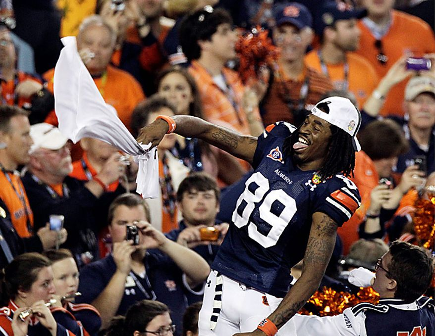 Auburn's Darvin Adams celebrates with fans after the BCS national championship NCAA college football game against Oregon on Monday, Jan. 10, 2011, in Glendale, Ariz. Auburn won, 22-19. (AP Photo/Charlie Riedel)