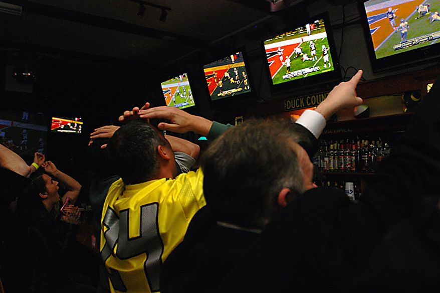 University of Oregon football fans react to a play on Monday, Jan. 10, 2011, in Taylor's bar in Eugene, Ore., as the Ducks went on to lose to Auburn, 22-19, in the BCS championship game. (AP Photo/Jeff Barnard)