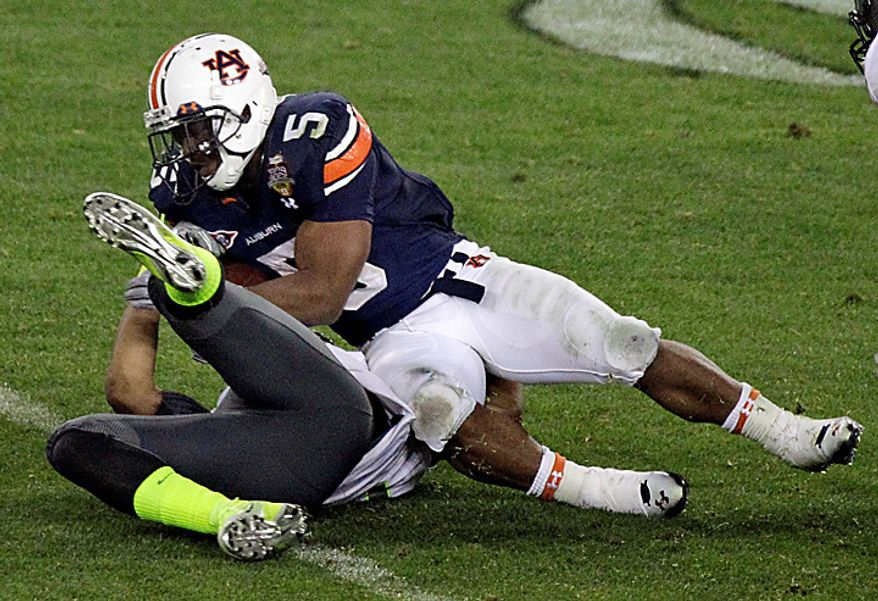 Auburn's Michael Dyer (5) rolls over Oregon's Eddie Pleasant as he carries the ball on a 37-yard gain during the second half of the BCS national championship NCAA college football game on Monday, Jan. 10, 2011, in Glendale, Ariz. Auburn won, 22-19. (AP Photo/Charlie Riedel)