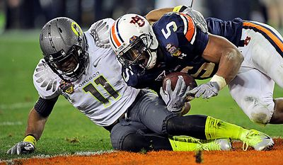 Auburn's Michael Dyer (5) is tackled short of the goal line as Oregon's Eddie Pleasant (11) defends during the second half of the BCS national championship NCAA college football game on Monday, Jan. 10, 2011, in Glendale, Ariz. Auburn won, 22-19. (AP Photo/Mark J. Terrill)