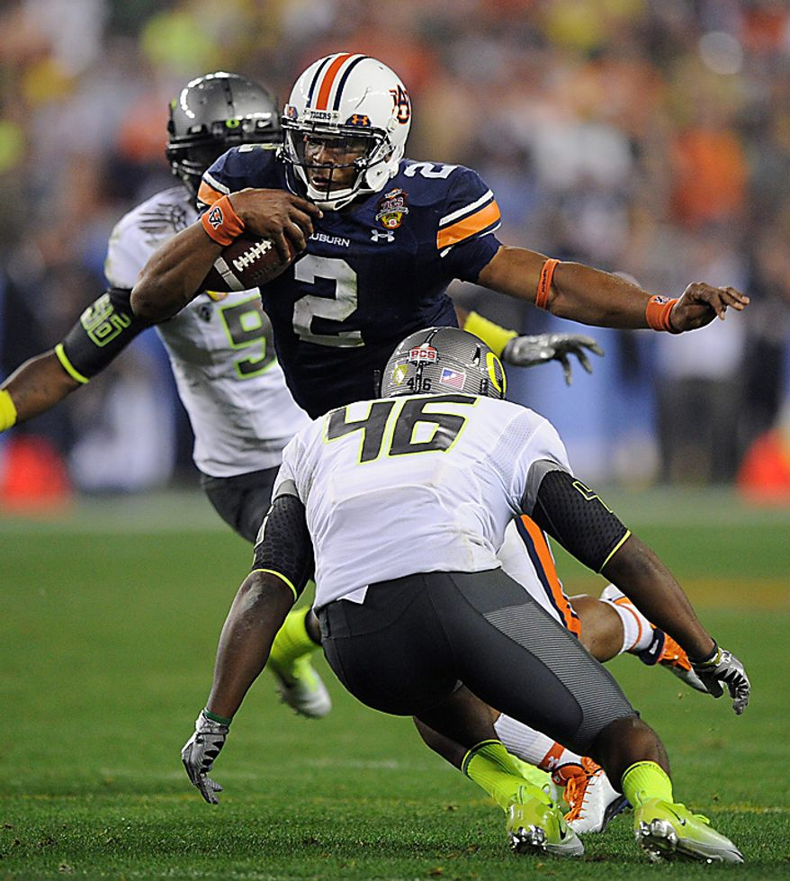 Auburn's Cam Newton runs with the ball as Oregon's Michael Clay (46) moves in during the second half of the BCS national championship NCAA college football game on Monday, Jan. 10, 2011, in Glendale, Ariz. (AP Photo/Mark J. Terrill)
