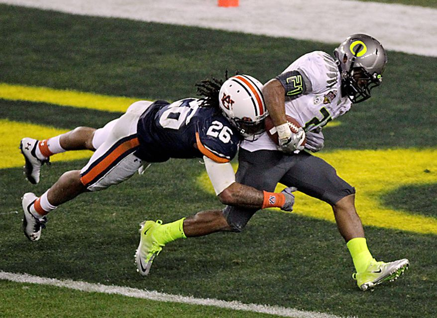 Oregon's LaMichael James (21) scores a touchdown as  Auburn's Mike McNeil defends during the second half of the BCS national championship NCAA college football game on Monday, Jan. 11, 2011, in Glendale, Ariz. (AP Photo/Charlie Riedel)