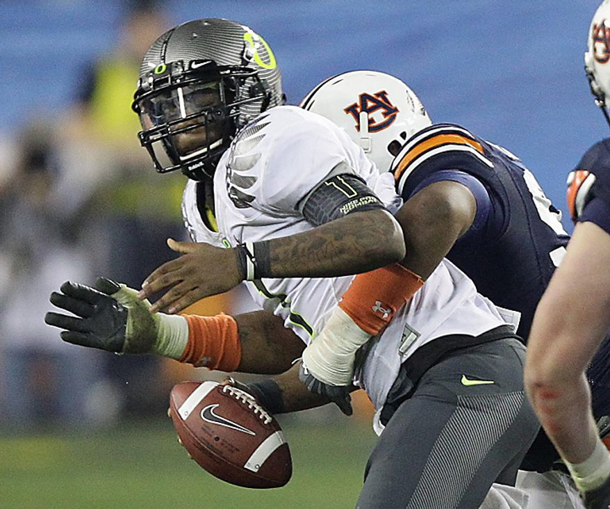 Oregon's Darron Thomas, left, fumbles as he is hit by Auburn's Nick Fairley during the second half of the BCS national championship NCAA college football game on Monday, Jan. 10, 2011, in Glendale, Ariz. Oregon recovered the fumble. (AP Photo/Matt York)
