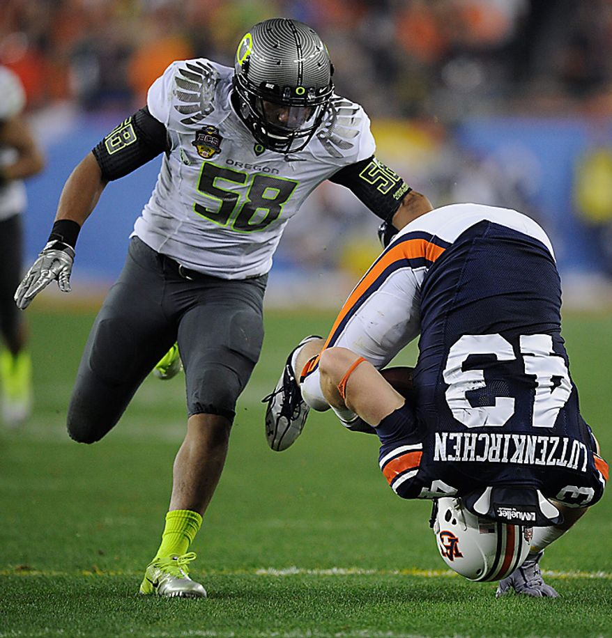 Auburn's Philip Lutzenkirchen (43) tumbles after making a catch as Oregon's Kenny Rowe defends during the second half of the BCS national championship NCAA college football game on Monday, Jan. 10, 2011, in Glendale, Ariz. (AP Photo/Mark J. Terrill)