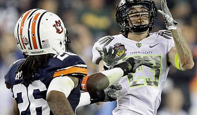 Oregon's Jeff Maehl (23) catches a pass as Auburn's Mike McNeil (26) defends during the first half of the BCS national championship NCAA college football game on Monday, Jan. 10, 2011, in Glendale, Ariz. (AP Photo/Matt York)