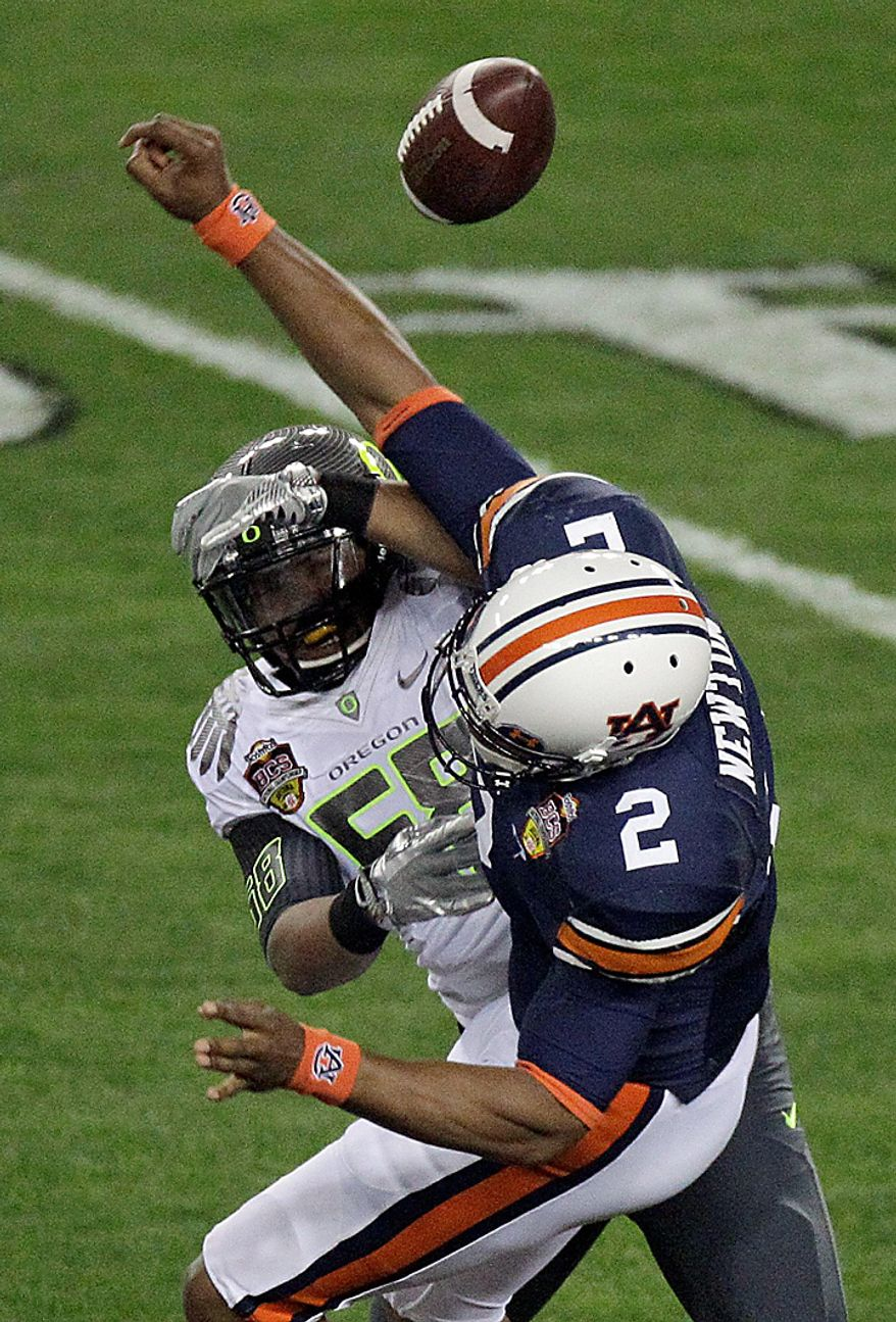 Auburn's Cam Newton (2) fumbles the ball as he is hit by Oregon's Kenny Rowe during the first half of the BCS national championship NCAA college football game on Monday, Jan. 10, 2011, in Glendale, Ariz. Auburn recovered the ball. (AP Photo/Charlie Riedel)