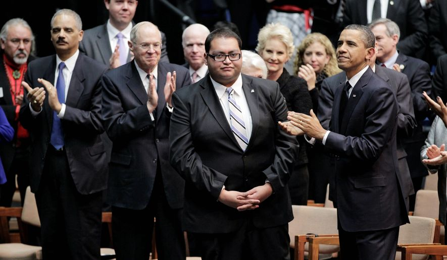 HONORED: President Obama joins the audience Wednesday during a memorial service in Tucson, Ariz., in applauding Daniel Hernandez, an intern for Democratic Rep. Gabrielle Giffords who helped her immediately after she was wounded Saturday during the shopping center shooting spree. (Associated Press)