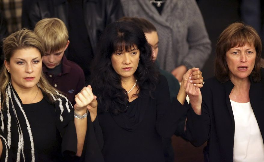 Roxanna Green (center), mother of 9-year-old shooting victim Christina Taylor Green, is shown during a community Mass at St. Odilia Catholic Church in Tucson, Ariz., on Tuesday, Jan. 11, 2011, to mourn the victims of Saturday's shooting. (AP Photo/Greg Bryan, Pool)