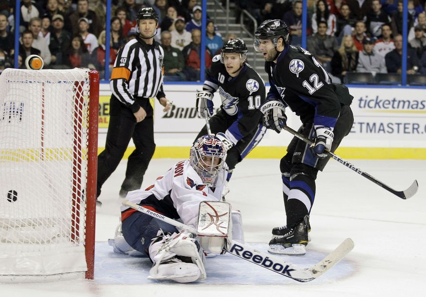 Tampa Bay Lightning left wing Simon Gagne (12) shoots the puck past Washington Capitals goalie Semyon Varlamov, of Russia (1) to score a second period goal during an NHL hockey game in Tampa, Fla., Wednesday, Jan. 12, 2011. Looking on is Lightning's Sean Bergenheim (10) and referee Steve Kozari (40). (AP Photo/Chris O'Meara)