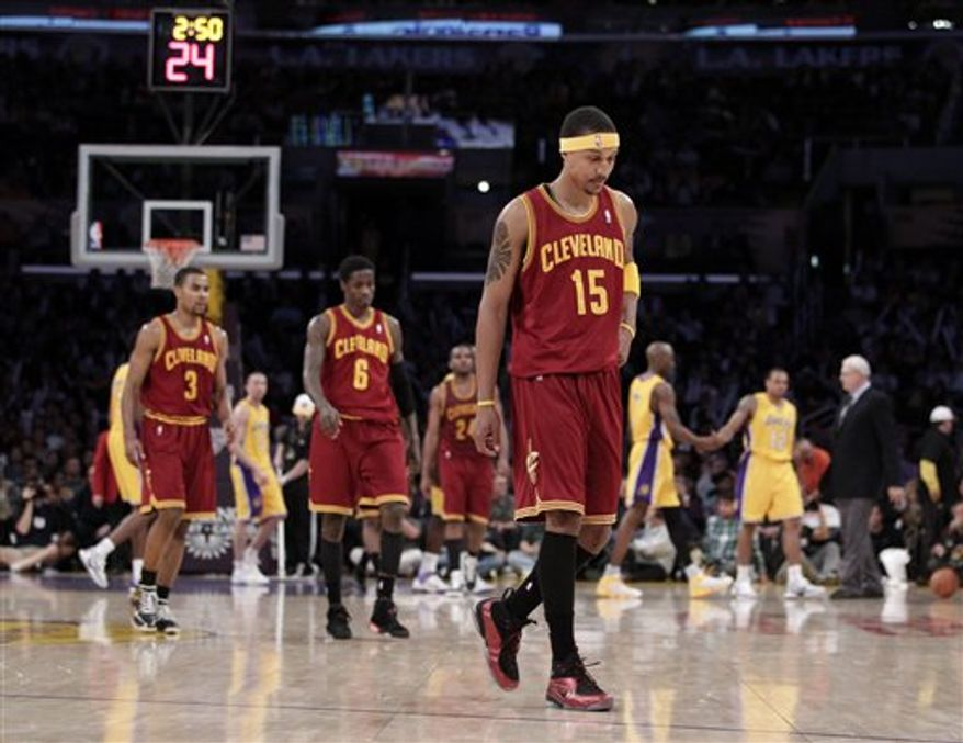 Cleveland Cavaliers guard Manny Harris, center, walks down the court as Los Angeles Lakers forward Pau Gasol, right, of Spain, is greeted by Kobe Bryant after Gasol made a basket during the first half of an NBA basketball game in Los Angeles, Tuesday, Jan. 11, 2011. (AP Photo/Jae C. Hong)