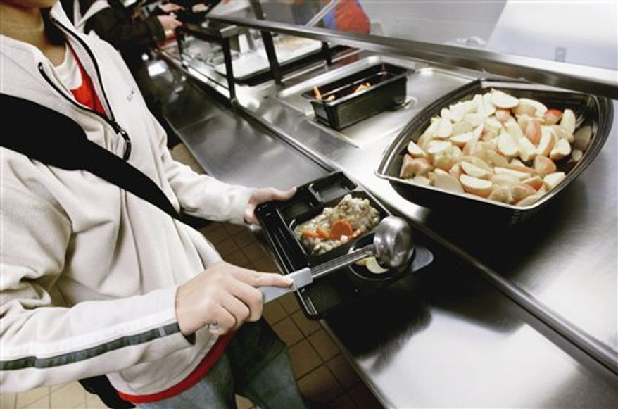FILE - In this Nov. 19, 2007, file photo, a student puts  apple slices on his tray during lunch at Central High School in St. Paul, Minn. Schoolchildren would have to pick up more whole grains, fruits and vegetables on the lunch line under proposed new federal standards for school lunches. The Agriculture Department proposal applies to lunches subsidized by the federal government and would be the first major nutritional overhaul of school meals in 15 years. They are expected to be announced Thursday, Jan. 13, 2011.   (AP Photo/Jim Mone, File)