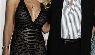 FILE - In this Sept. 24, 2008 file photo, Holly Madison, left, and Hugh Hefner arrive at the Fox Reality Channel Really Awards in Los Angeles.  (AP Photo/Matt Sayles, file)