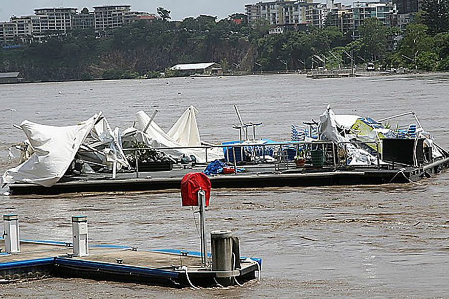 The remains of a floating restaurant called Drift Cafe is swept down the Brisbane River Wednesday, Jan. 12, 2011, as floodwaters surge through Brisbane, Australia. At least 22 people have died and more than 40 are missing across Australia's northeastern state of Queensland since drenching rains that began in November sent swollen rivers spilling over their banks, flooding an area larger than France and Germany combined. (AP Photo/Ken Merrin)