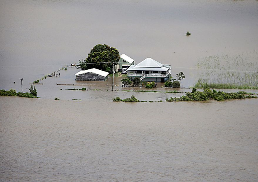 A house is surrounded by flood water near Grafton, in Australia's New South Wales state, Wednesday, Jan. 12, 2011. Deadly floodwaters that have cut a swath across northeastern Australia flowed onto the streets of the nation's third-largest city, Brisbane, forcing people to flee suburbs and skyscrapers. (AP Photo/Wolter Peeters, Pool)