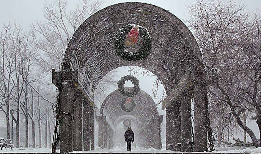 A morning commuter passes under the trellis row at Christopher Columbus Park in Boston, Wednesday, Jan. 12, 2011.  The Boston area is expected to receive well over a foot of snow during a day long winter storm.(AP Photo/Charles Krupa)