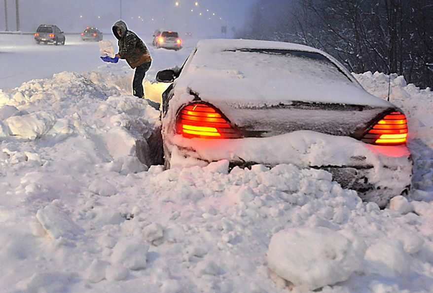 Roy Williams of Westfield, Mass., shovels snow in front of his vehicle on a merge ramp on Interstate 91 southbound during a winter storm in Windsor, Conn., Wednesday, Jan. 12, 2011.  Williams said a plow clearing the highway passed by and blocked him in.  (AP Photo/Jessica Hill)