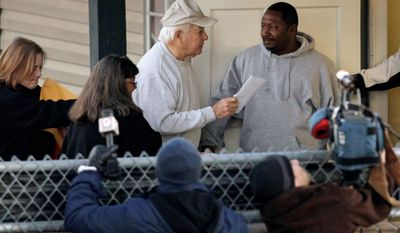 Former Louisiana Gov. Edwin Edwards (in hat) arrives with his daughter Anna Edwards (far left) at a Baton Rouge halfway house Thursday to begin serving the rest of his prison sentence. He was released after serving eight years for a corruption conviction. (Associated Press)