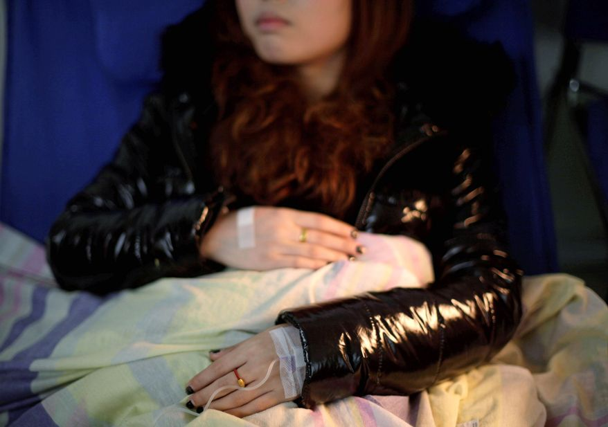 Zhang Jie, 22, sits in the recovery room Dec. 13 after her second abortion in two years at a clinic in Xi'an, China. While exact numbers are hard to come by, official figures show abortions are increasing, and experts say many of the abortion-seekers are young, single women. (Associated Press)