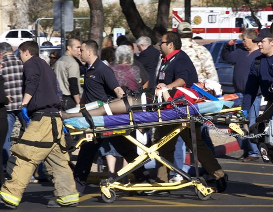 "FILE - In this Jan. 11, 2011 file photo, Dr. Peter Rhee, Trauma and Critical Care Emergency Surgery doctor at University Medical Center, describes in more detail the gunshot wound Rep. Gabrielle Giffords, D-Ariz.,received on Saturday, during a news briefing at UMC in Tucson, Ariz. Giffords remains in critical condition, but doctors have reported steady progress each day since she was wounded last weekend. If all goes well, she may be ""out of the woods"" on Friday, said Rhee. (AP Photo/Ross D. Franklin, File)"