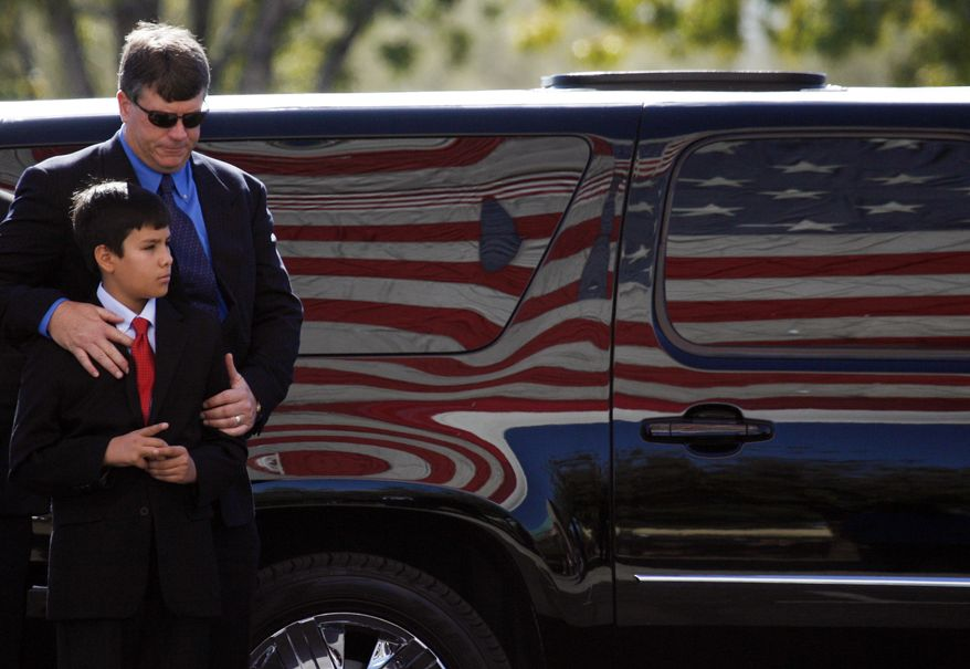 John Green and son Dallas, the respective father and brother of 9-year-old Christina Green, arrive at the St. Elizabeth Ann Seton Church for Christina's funeral on Thursday, Jan. 13, 2011, in Tucson, Ariz. Green was the youngest victim of Saturday's shooting in Tucson. (AP Photo/Mamta Popat, Pool)