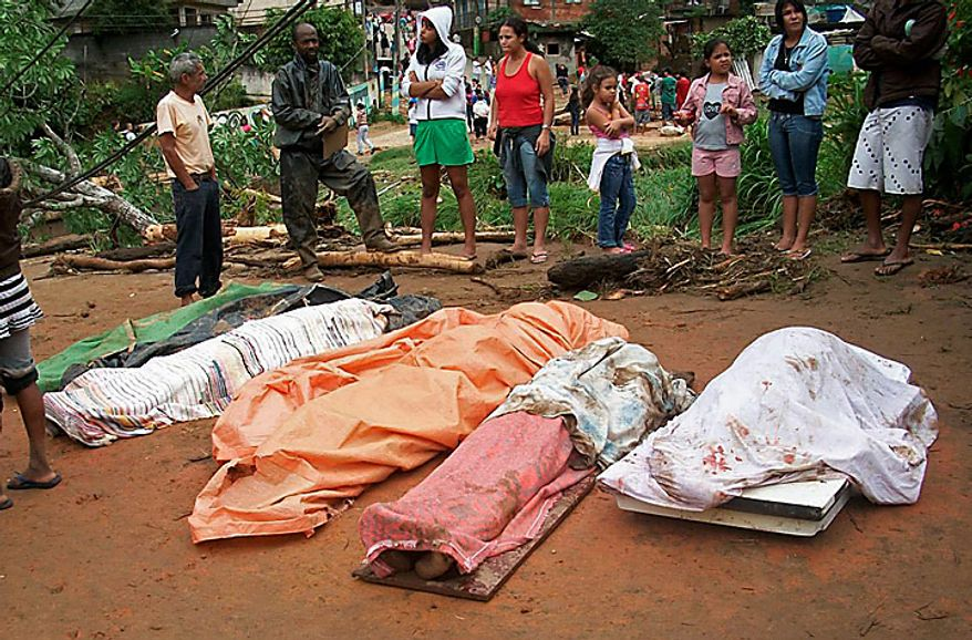 People stand by the bodies of mudslide victims after heavy rain in the neighborhood of Caleme in Teresopolis, Brazil, Wednesday Jan. 12, 2011.  Authorities in Rio de Janeiro say 58 people have died in the mudslides and flash floods that followed torrential rain overnight. The mayor of the mountain town of Teresopolis just north of Rio said in a statement Wednesday that 48 people died, and more than 1,000 have been left homeless. (AP Photo/Paulo Cezar, Agencia O Globo)