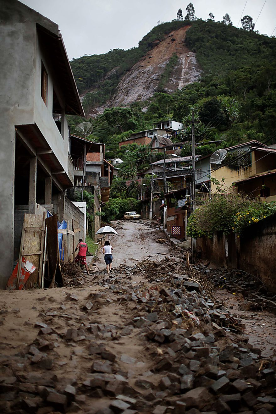 People walk among debris after landslides at Caleme neighborhood in Teresopolis, Brazil, Thursday, Jan. 13, 2011. Driving rains sent tons of rusty red earth sliding into Brazilian mountain towns, killing hundreds of people and leaving dozens more missing _ lives rescuers hoped to save as they resumed searches Thursday. (AP Photo/Felipe Dana)
